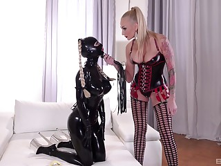 Mistress plays dominant with resulting girl dressed alongside latex costume